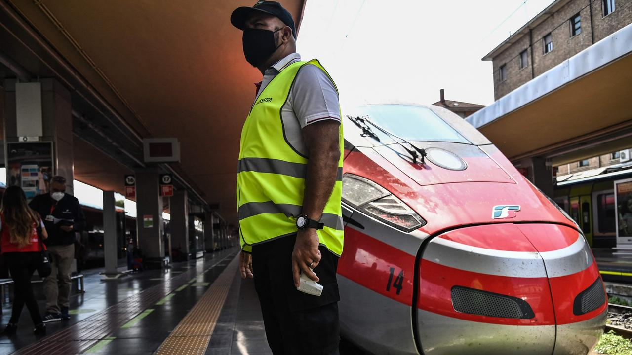 """An attendant waits to check the body temperature of passengers boarding a high-speed """"Frecciarossa"""" train at the Porta Nuova railway station in Turin. Since early August, Italy has required proof of vaccination, recent recovery from coronavirus or a negative test for people wanting to dine indoors or enter museums and sports events. Picture: Marco Bertorello / AFP"""