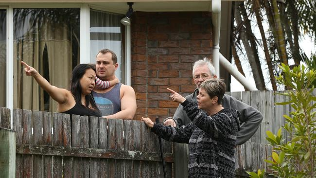 Police and emergency services at the scene of a house fire in Carrara. Neighbours look on. Picture Glenn Hampson