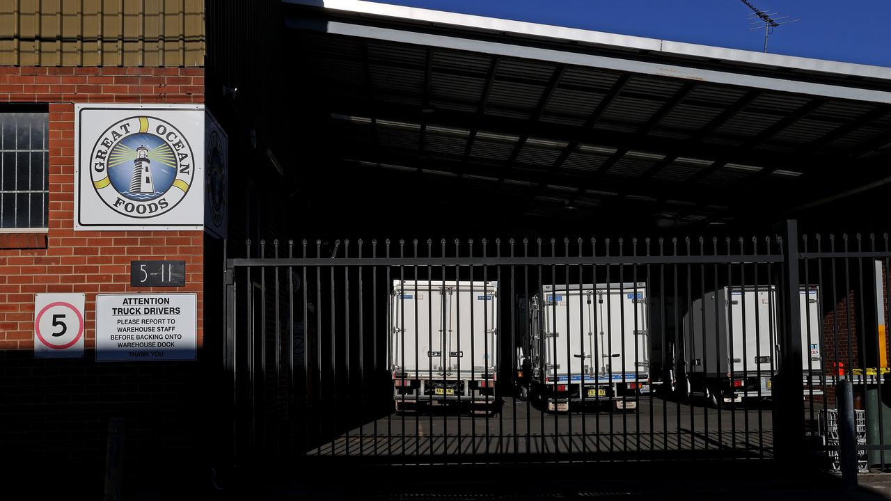Trucks at Great Ocean Foods sit behind locked gates in Marrickville after two cases reported on Saturday were linked to the site. Picture: NCA NewsWire/Dylan Coker
