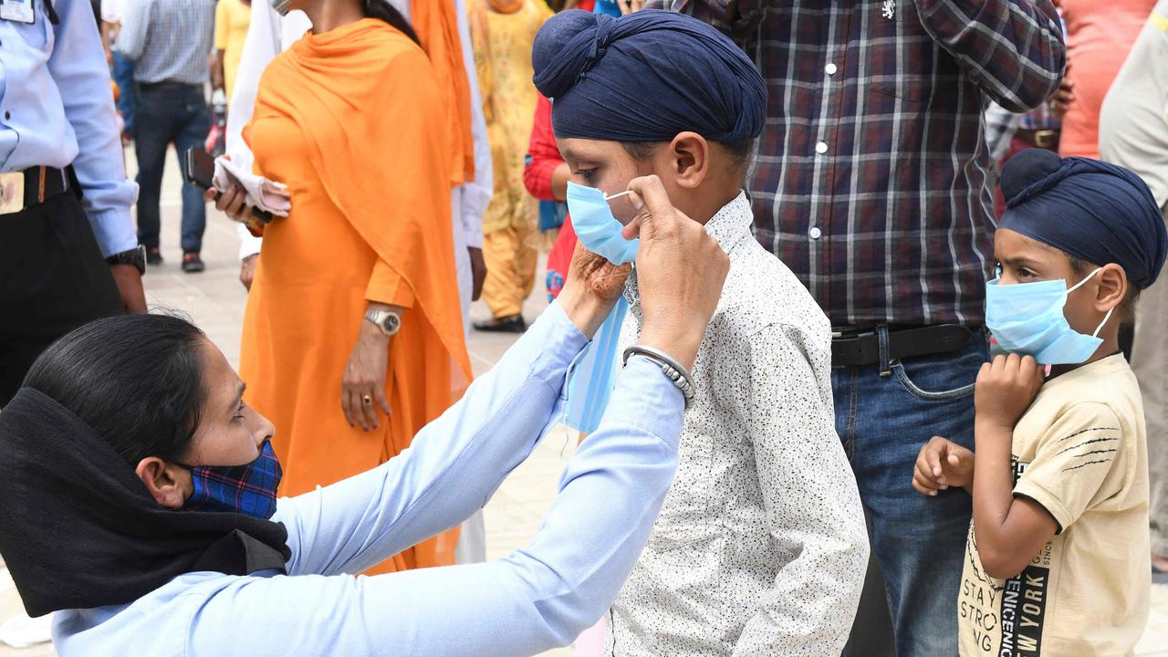 A guard attaches a mask to boy in Amritsar in Punjab last weekend. Picture: Narinder Nanu/AFP