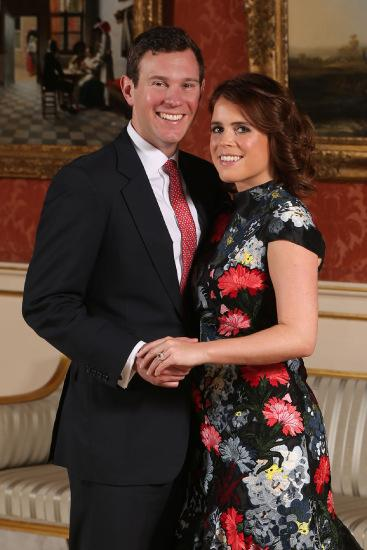 Britain's Princess Eugenie of York (R) poses with her fiance Jack Brooksbank in the Picture Gallery at Buckingham Palace in London on January 22, 2018, after the announcement of their engagement.  Britain's Princess Eugenie of York wears a dress by Erdem, shoes by Jimmy Choo and a ring containing a padparadscha sapphire surrounded by diamonds. Britain's Princess Eugenie of York has got engaged, Buckingham Palace announced January 22, 2018, lining up a second royal wedding this year at the church where Prince Harry will tie the knot.  / AFP PHOTO / POOL / Jonathan Brady