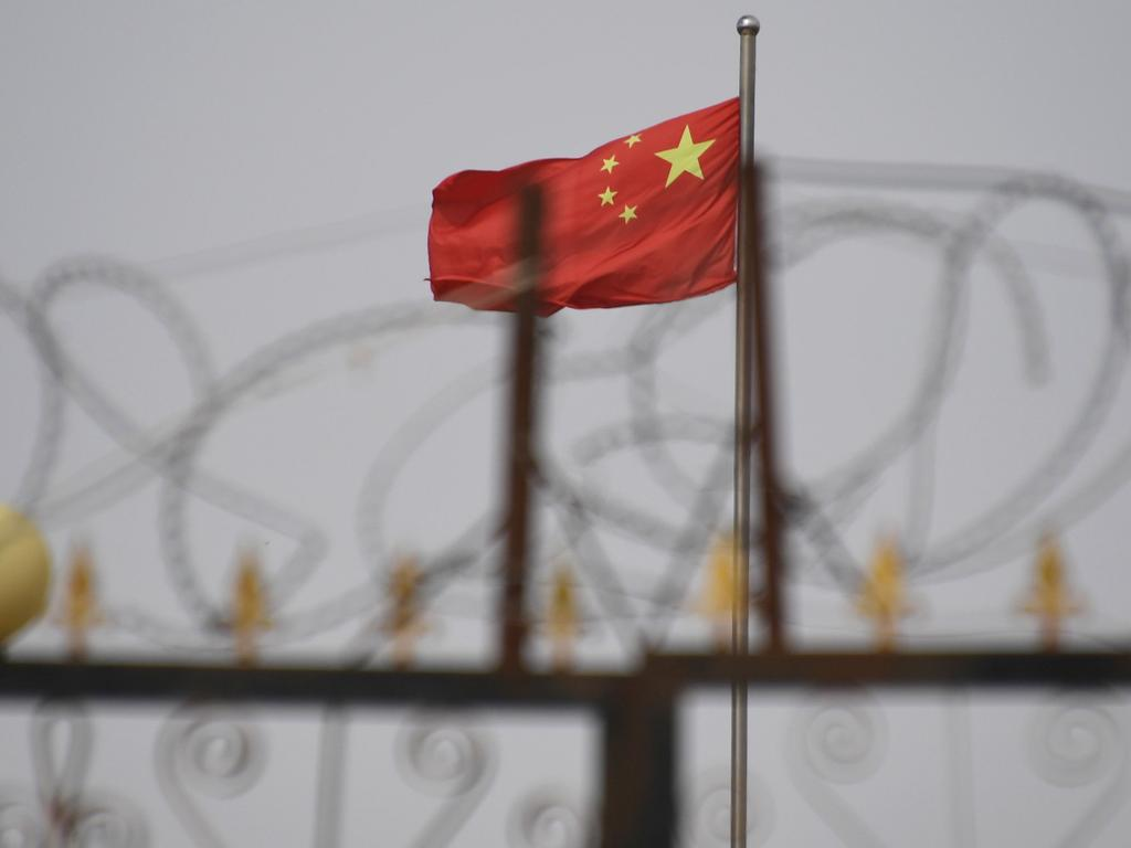 A Chinese flag behind razor wire at a housing compound in Yangisar, south of Kashgar, in China's western Xinjiang region. Picture: Greg Baker/AFP
