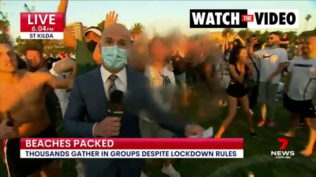 7 News reporter surrounded by hundreds of Melburnian beachgoers (7 News)