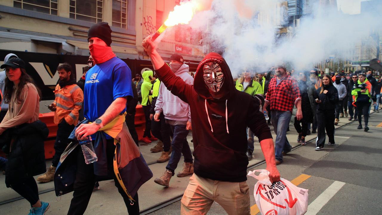 A man wearing a Guy Fawkes mask waves a flare during a wild protest in Melbourne on Tuesday. Picture: Aaron Francis