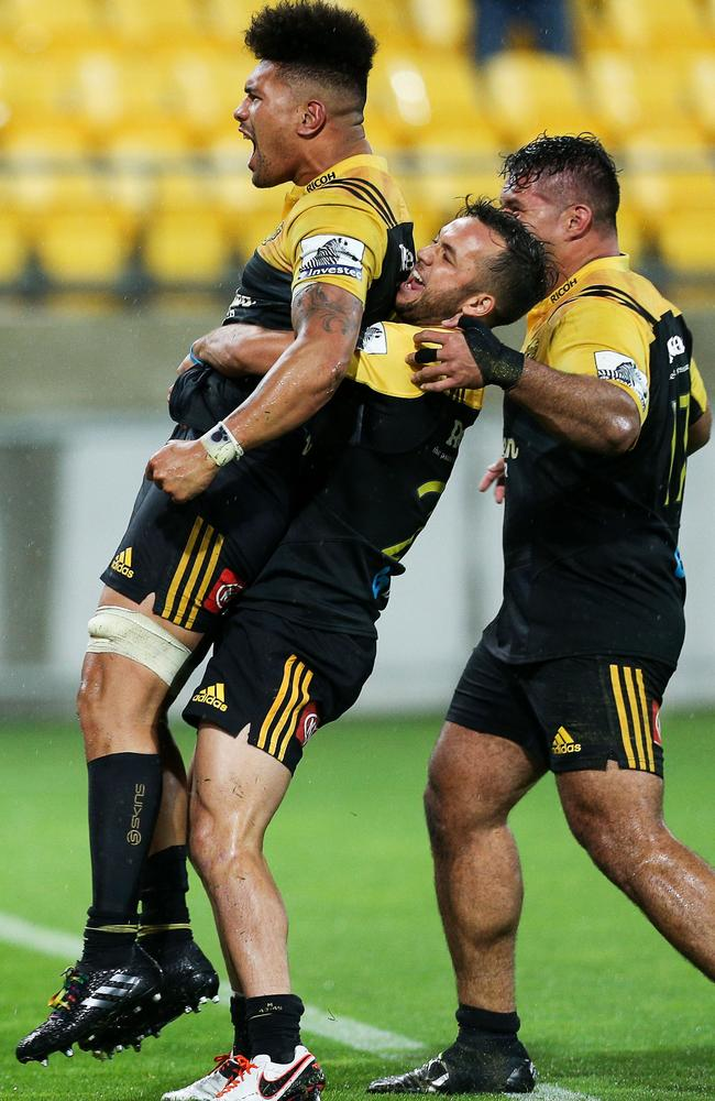 Ardie Savea of the Hurricanes is congratulated on his match-winning try by teammates.