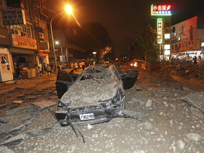 A crushed vehicle sits in rubble on a destroyed street after multiple explosions from an underground gas leak in Kaohsiung, Taiwan.