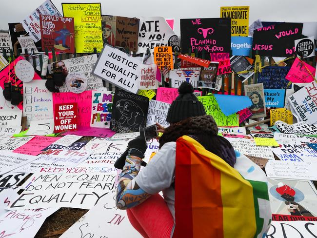 Protesters build a wall of signs outside the White House for the Women's March on Washington. Picture: AP Photo/John Minchillo