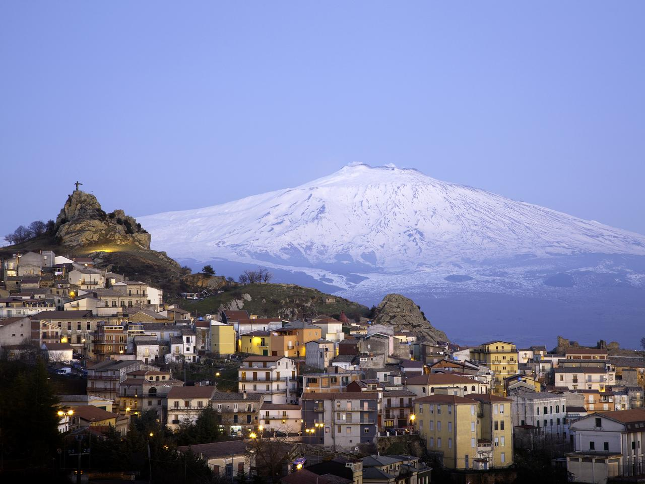 View of the village of San Teodoro and Etna volcano on background. Sicily, Italy.