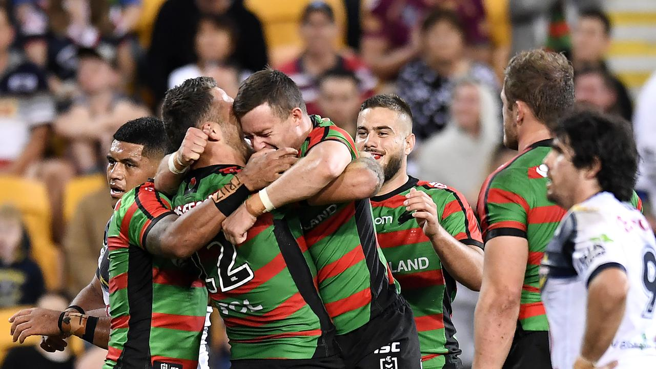 Damien Cook celebrates with teammates after scoring a try