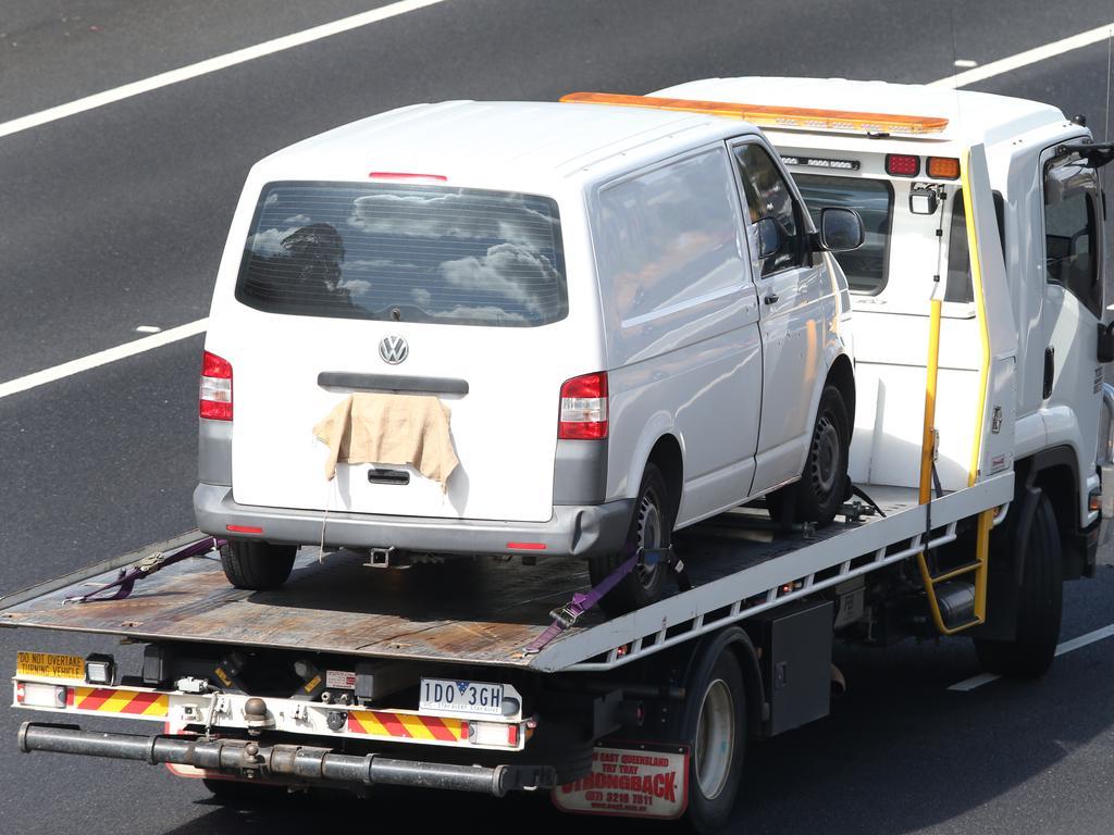 Several gunshot holes can be seen in the driver's side door as Paul Virgona's van is taken away on the back of a tow truck. Picture: David Crosling