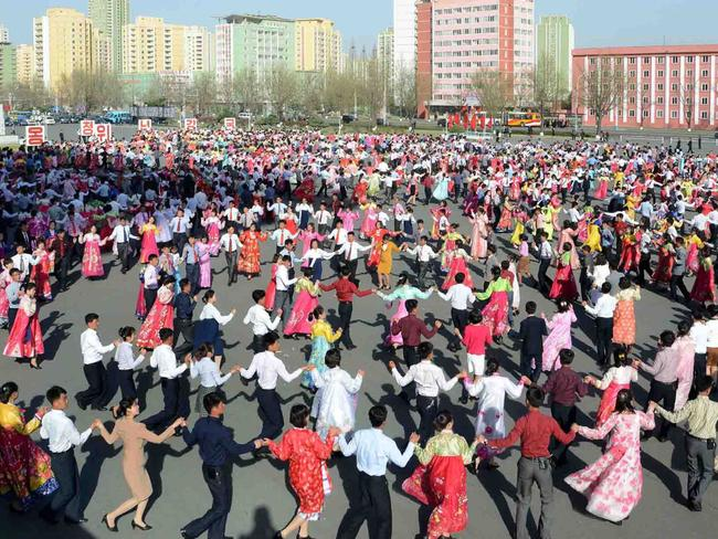 People dance to celebrate the 105th anniversary of their founding president. Picture: AFP