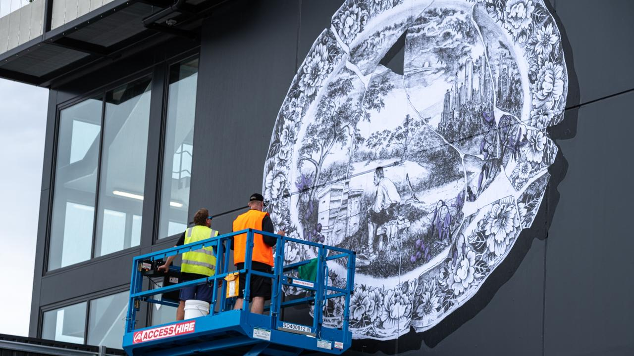 Robert Hague installs a paste-up on the rear wall of the development.