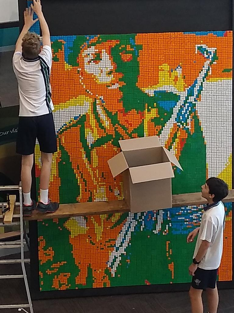 Elijah Lewis and his friend Tom work on the final touches of the mural. Picture: World Vision