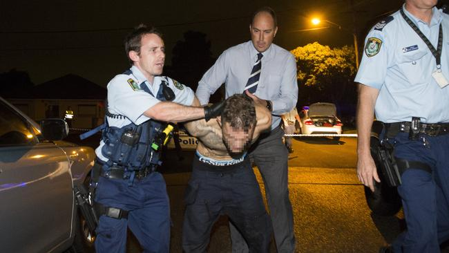 Police arrest a male at the scene of a homicide in Bankstown. Picture: Chris McKeen