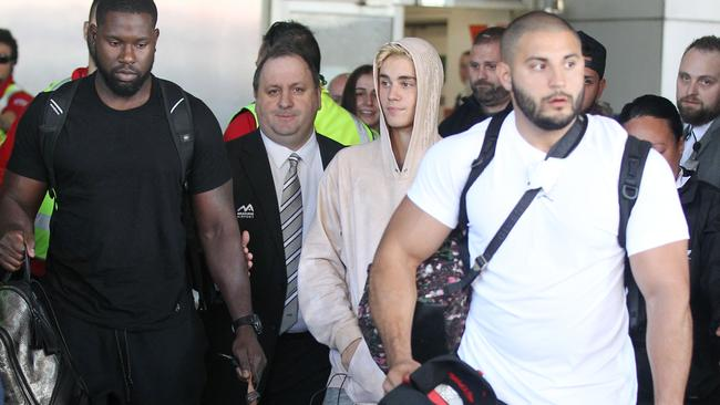 Justin Bieber arrives into Melbourne with his bodyguard in the white shirt.