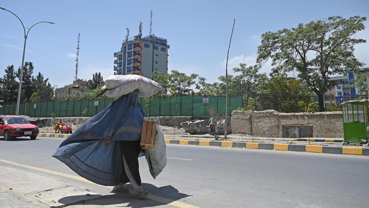 A burqa clad woman carrying a sack on her head walks along a road in Kabul on August 7, 2021. Picture: Sajjad Hussain/AFP