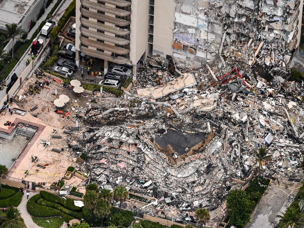 This aerial view shows search and rescue personnel working on site after the partial collapse of the Champlain Towers South in Surfside, north of Miami Beach on June 24. (Photo by CHANDAN KHANNA / AFP)