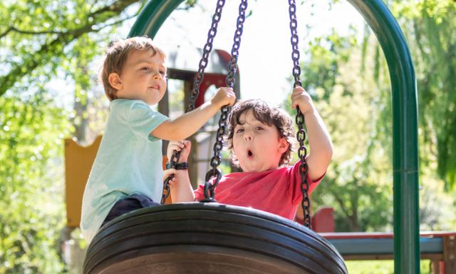 Laughing Three years old children, one hispanic and one caucasian, playing in the park playground swing