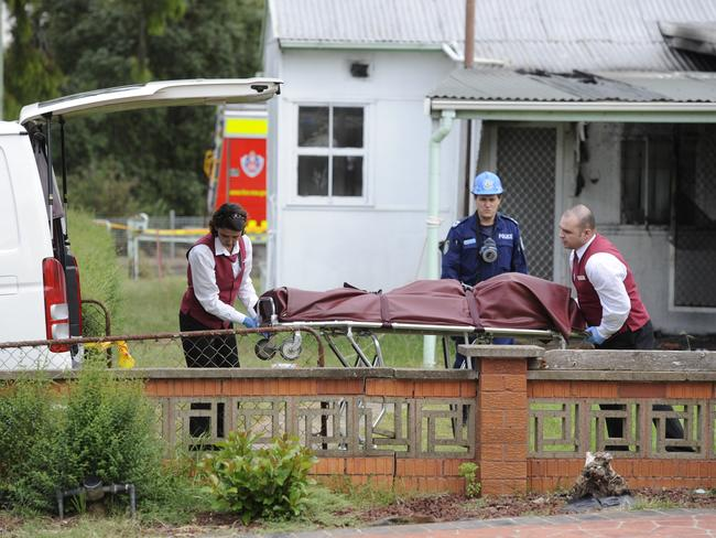 The man's body is removed from the house after the fatal fire. Picture: Phillip Rogers