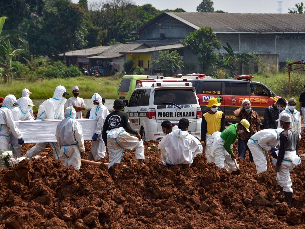 Workers bury the bodies of Covid-19 coronavirus victims at the Pedurenan public cemetery in Bekasi, West Java.