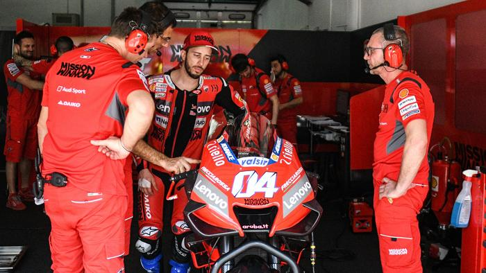 Andrea Dovizioso prepares to mount his bike.