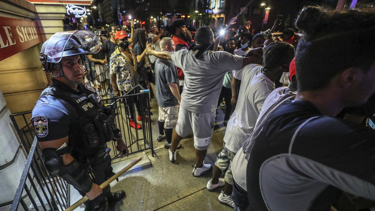 Protesters surround a police officer in Louisville, Kentucky on May 28 during a protest for Breonna Taylor, a black woman fatally shot by police in her home in March. Picture: Michael Clevenger/Courier Journal via AP