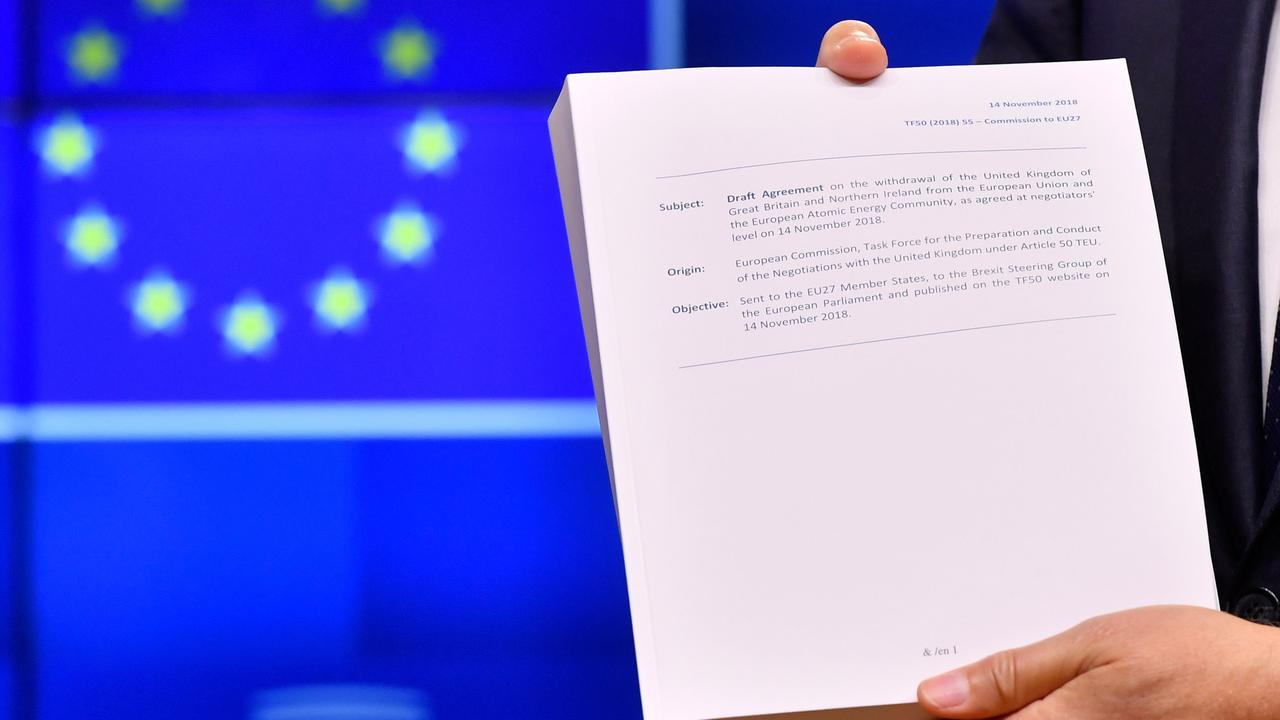 """European Council President Donald Tusk holds the """"draft agreement of the withdrawal of the United Kingdom of Great Britain and Northern Ireland from the European Union."""
