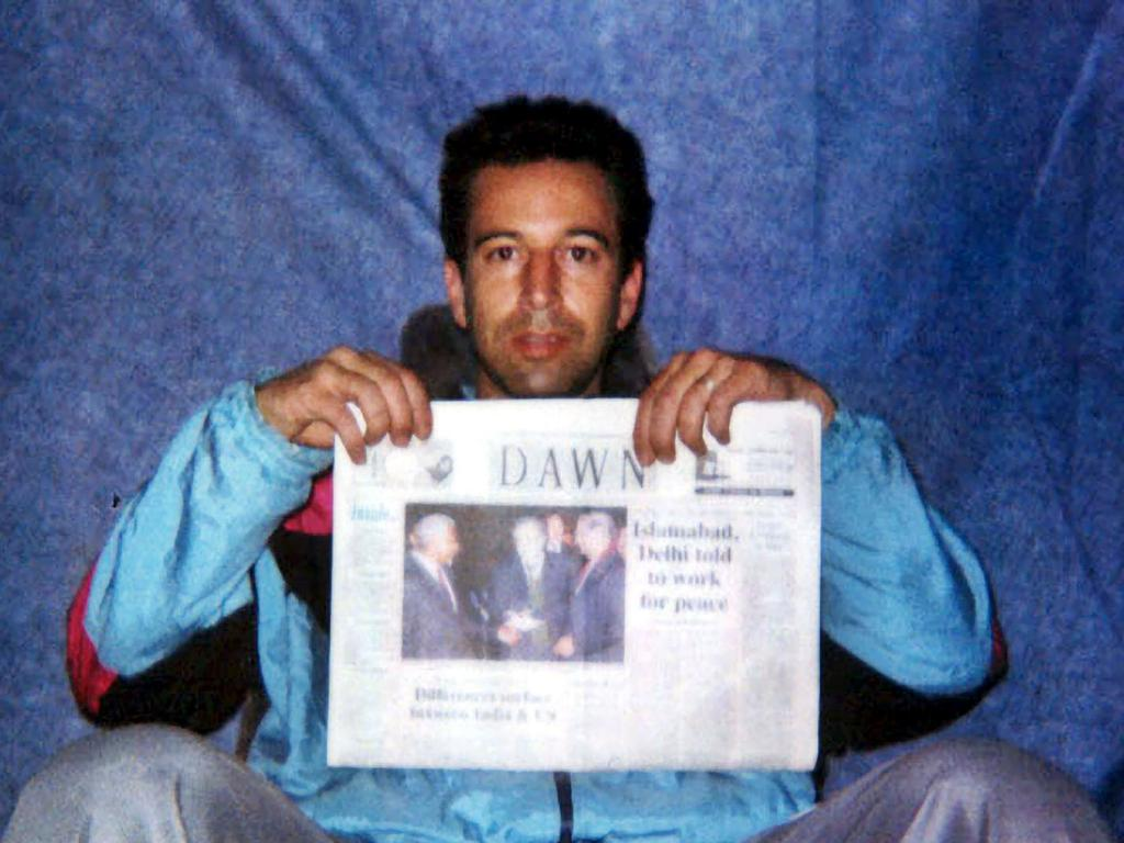 Wall Street Journal reporter Daniel Pearl at an undisclosed location with a copy of Pakistan's English language newspaper Dawn. Picture: The Washington Post/AFP