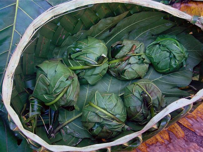 At a Toonai Fish, chicken, pork and other meats are wrapped in banana leaves with coconut cream and various vegies before being cooked over red hot stones on an open fire, called an umu. After two hours the food is unwrapped, the meal is served, and it is communally enjoyed. Picture: Flickr/Polynesian Xplorer
