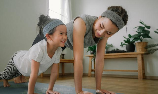 Sport young asian woman work out with little girl at home