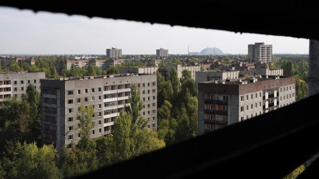 Pripyat rooftops, view through a ventilation slot in the roof space of a residential tower block. The power plant, complete with the New Arch, can be seen on the horizon. Picture: Darmon Richter/FUEL Publishing