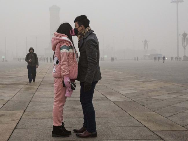 A Chinese couple wear masks as they kiss during a day of high pollution in Tiananmen Square on December 1. Picture: Kevin Frayer/Getty Images